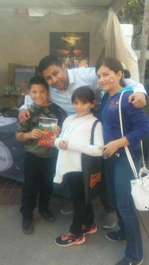 Author Nick Sharma stops to take a picture with a fan at the LA Festival of Books showcasing Sharma's first novel How to be a Hero