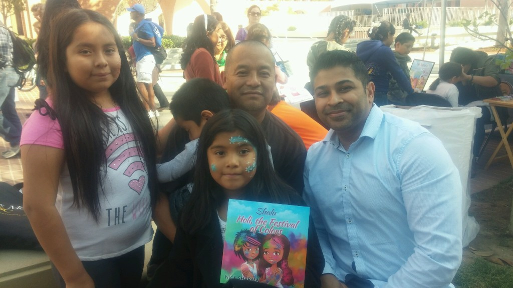 Author Nick Sharma stops to take a picture with a family at the LA Festival of Books showcasing Holi, The Festival of Colors