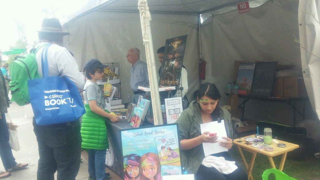 Authors Nick Sharma and Ron Lovell speak to some fans about their books at the LA Festival of Books while face painter Karina Ramirez gets ready