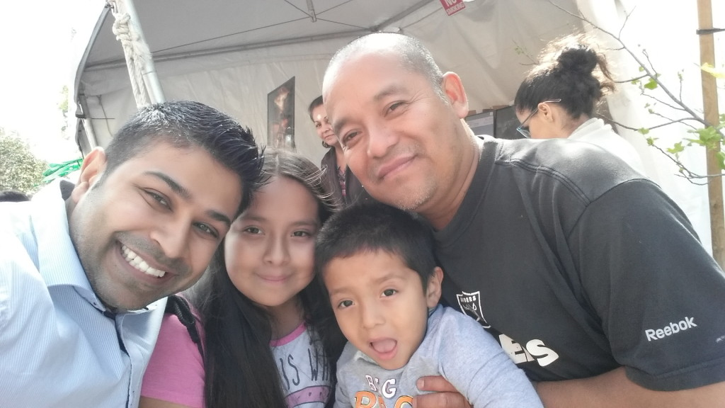 Author Nick Sharma takes a selfie with some kids as they wait with their dad for some facepainting at the LA Festival of Books for the premiere of Holi, The Festival of Colors